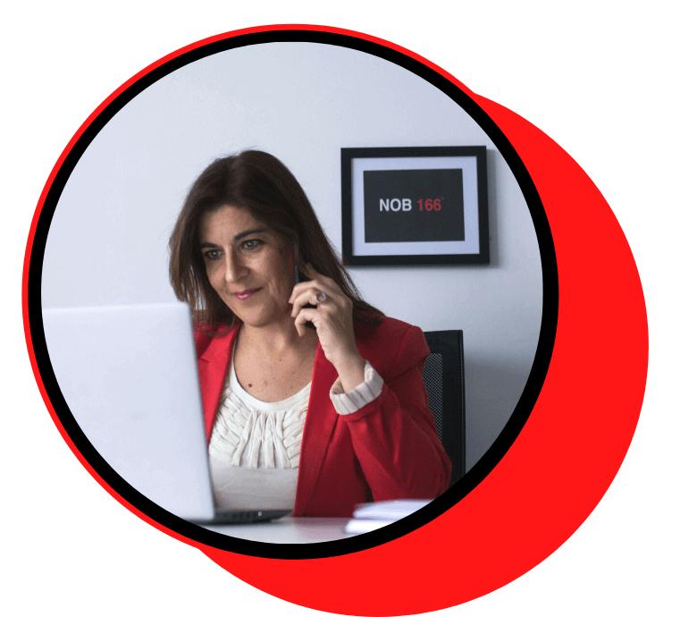 mujer con americana roja hablando por el movil y escribiendo en el ordenador